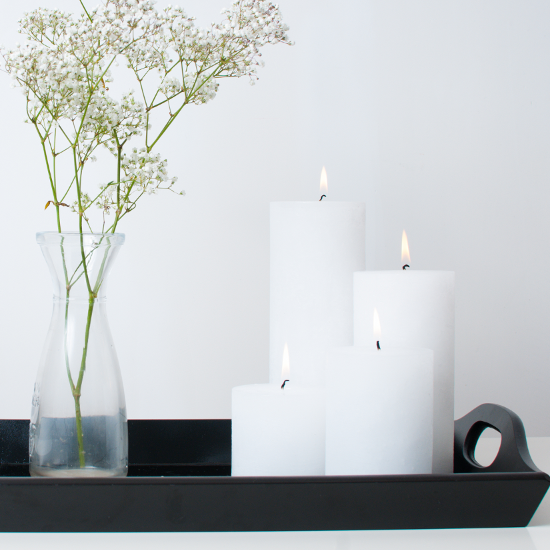 Four white pillar candles beside a carafe shaped glass vase filled with gypsophila displayed on black wooden tray.